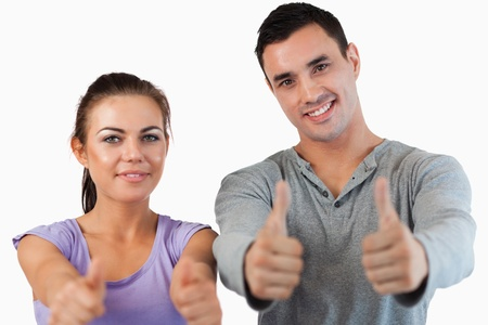 Young couple giving thumbs up against a white background photo