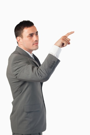 Portrait of a young businessman pressing an invisible key against a white background photo