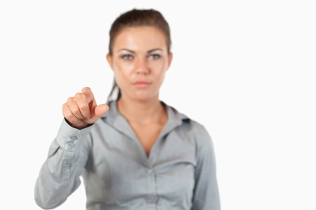 Gorgeous businesswoman pressing an invisible key against a white background photo