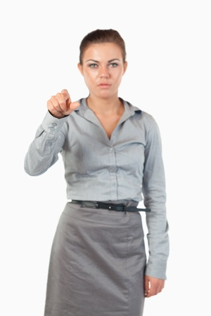 Portrait of a gorgeous businesswoman pressing an invisible key against a white background photo
