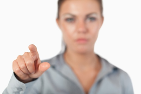 Young businesswoman pressing an invisible key with the camera focus on her hand photo