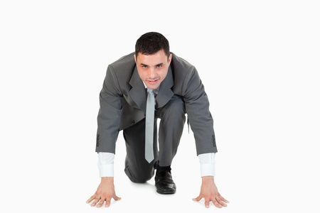 willingness: Businessman in the starting blocs against a white background