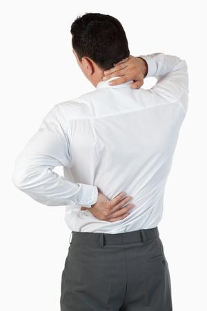 Porträt des schmerzenden Rücken von einem Geschäftsmann vor einem weißen Hintergrund