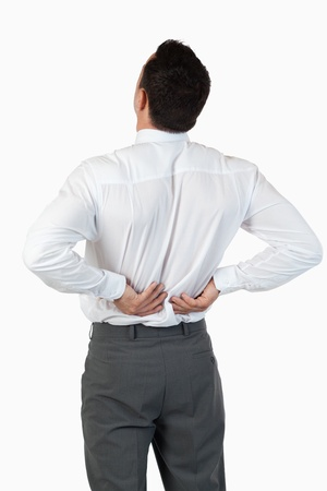 Portrait of the painful back of a young businessman against a white background photo
