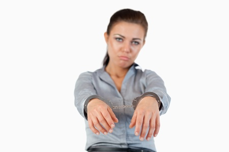 Businesswoman with handcuffs against a white background photo