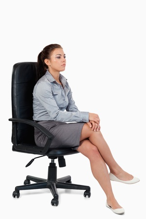 Portrait of a serious businesswoman sitting on an armchair against a white background photo