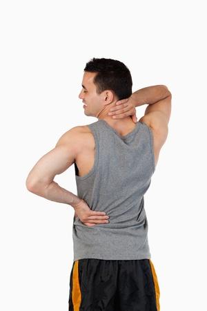 sportmassage: Portret van een sportieve man met een pijn in de rug tegen een witte achtergrond