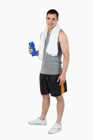 Young man with a bottle after training against a white background photo