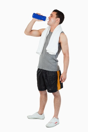 Young male drinking after workout against a white background Stock Photo - 11624563