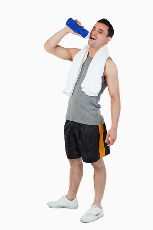 Young man drinking water after workout against a white background photo