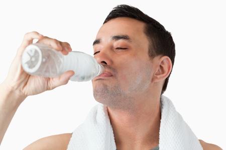 sorbo: Hombre joven que goza de un sorbo de agua despu�s del entrenamiento sobre un fondo blanco