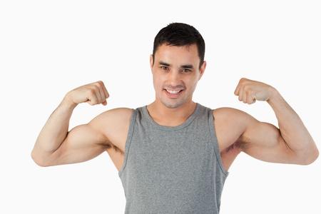 Varón joven que muestra sus músculos sobre un fondo blanco