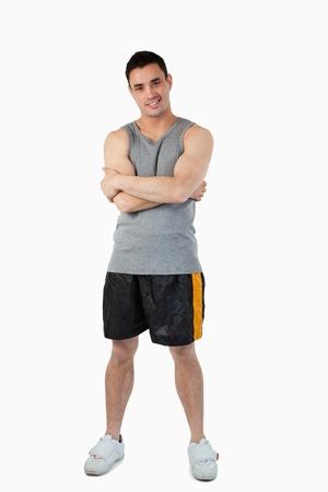 Masculino deportivo joven con los brazos cruzados sobre un fondo blanco