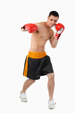 Young boxer performing a right hook against a white background photo