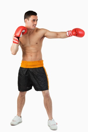 Side view of boxer hitting straight against a white background photo