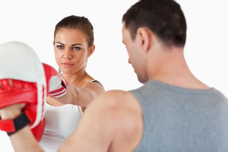 Young female with her martial arts trainer against a white background photo