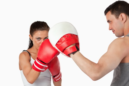Female boxer with strong fighting spirit against a white background photo