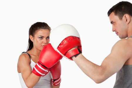 Female boxer focused on her training against a white background photo