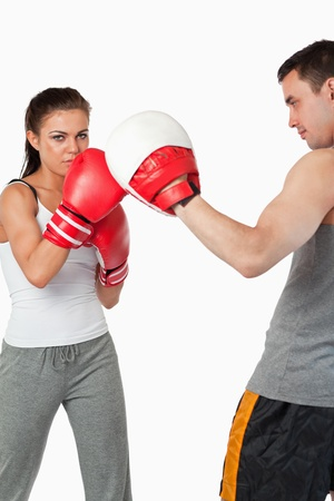 Young female training boxing against a white background photo