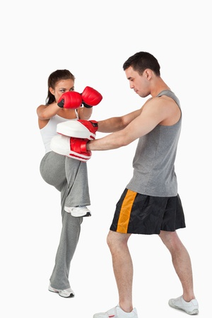 Female kickboxer practicing her knee technique against a white background photo