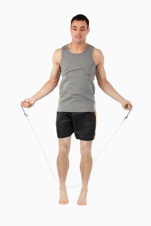 saltar la cuerda: Cuerda deportista joven saltando sobre un fondo blanco