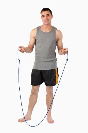 Deportista joven preparándose para saltar cuerda sobre un fondo blanco