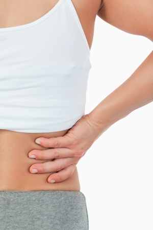 Close up of female with back pain against a white background photo