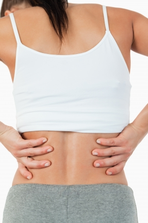 back injury: Back view of female with back pain against a white background Stock Photo
