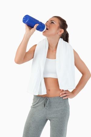 Mujer joven tomando un sorbo de su botella después del entrenamiento sobre un fondo blanco Foto de archivo - 11636623