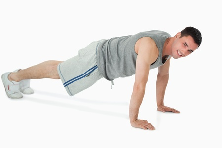 Side view of man doing push ups against a white background photo