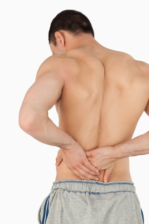 backpain: Young male suffering from back pain against a white background Stock Photo