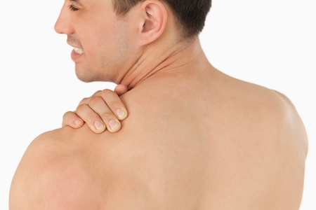 Young man with neck pain against a white background photo