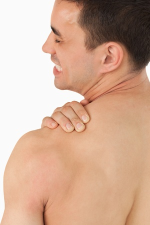 Young male experiencing neck pain against a white background photo