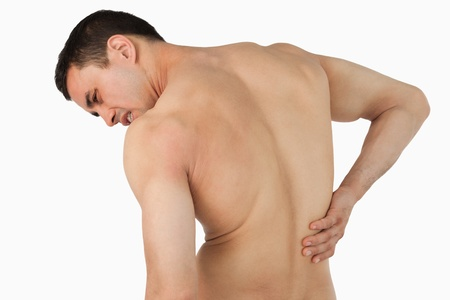 backpain: Back view of male suffering from back pain against a white background Stock Photo