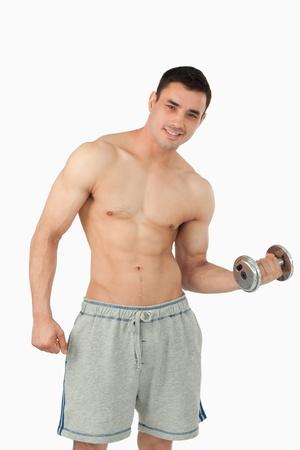Jeune homme faisant l'haltérophilie contre un fond blanc