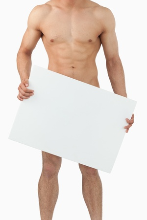 naked people: Sporty male body holding banner against a white background Stock Photo