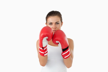 Female boxer in defensive stance against a white background photo