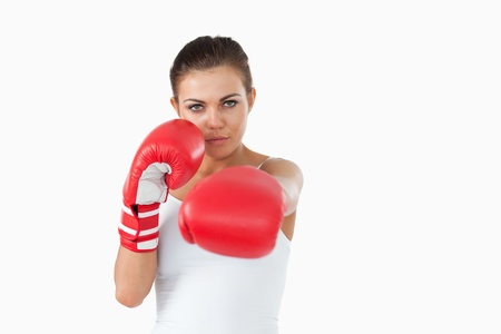Young female boxer attacking with her left against a white background photo