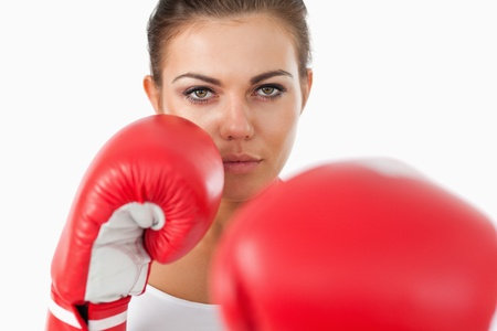 Female boxer attacking with her left against a white background photo