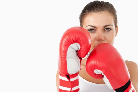 Female boxer taking cover behind her fists against a white background photo