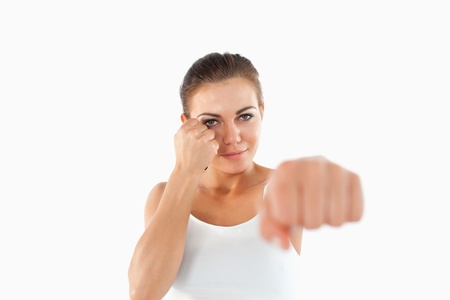 Female martial arts fighter attacking with her fist against a white background photo