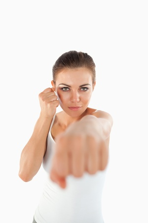 Female martial arts fighter striking with her fist against a white background photo