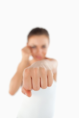 Left fist of female martial arts fighter attacking against a white background photo