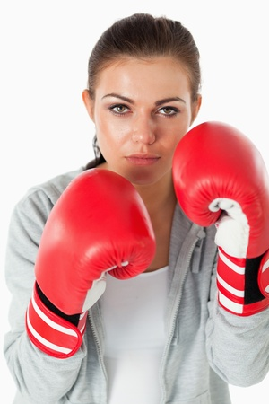 Portrait of a young woman with boxing gloves against a white background photo