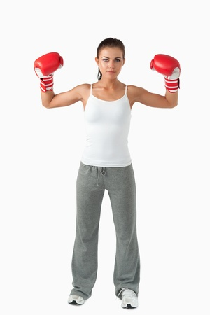 Portrait of a female boxer standing up against a white background photo
