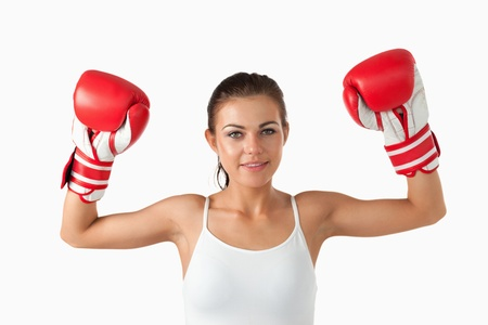 Female boxer raising her arms against a white background photo