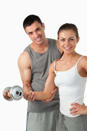 Portrait of a smiling man helping a woman to work out against a white background photo