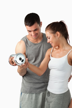 Portrait of a handsome man helping a woman to work out against a white background photo