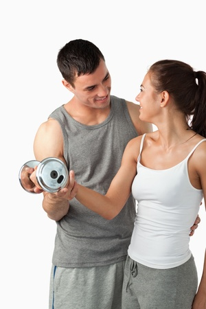 Portrait of a man helping a young woman to work out against a white background photo