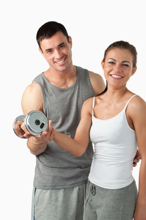 Portrait of a man helping a smiling woman to work out against a white background photo